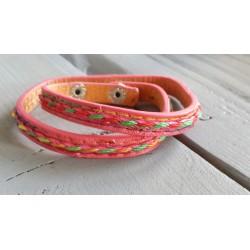 roze armband met gekleurd draad erop geborduurd